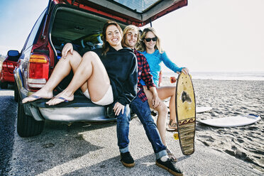 Caucasian friends sitting in car hatch with skateboard - BLEF00256