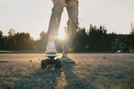 Legs of Caucasian teenage girl standing on skateboard - BLEF00280