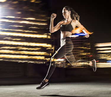 Double exposure of Caucasian woman running in city at night - BLEF00289