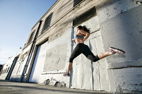 Mixed race woman running and jumping on sidewalk - BLEF00331