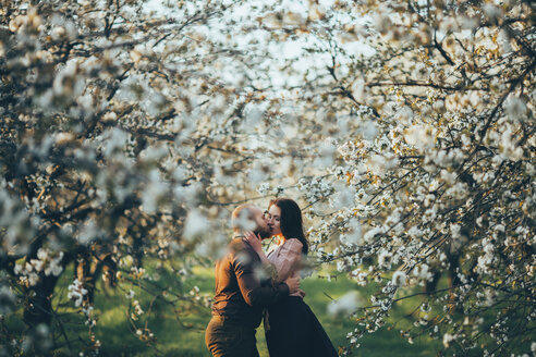 Caucasian couple kissing near blooming trees - BLEF00376