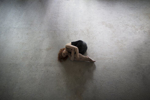 Caucasian woman laying on concrete in fetal position - BLEF00406