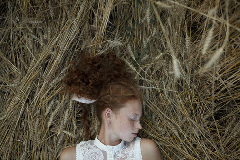 Serious Caucasian girl with freckles laying in wheat - BLEF00430