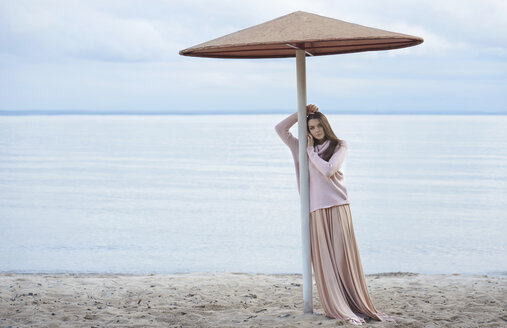 Pensive Caucasian woman leaning on beach umbrella - BLEF00496