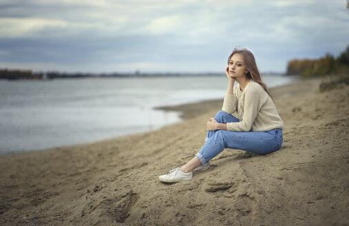 Pensive woman sitting on beach - BLEF00499
