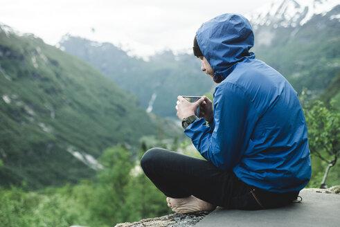 Caucasian man sitting in mountain landscape drinking coffee - BLEF00553