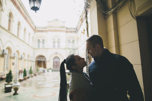 Caucasian couple standing face to face in courtyard - BLEF00583