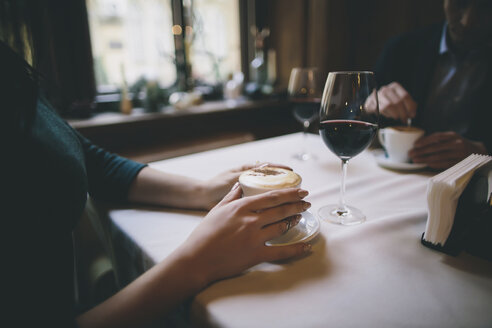 Hands of Caucasian couple drinking coffee and wine - BLEF00589