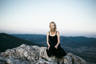 Caucasian woman sitting on rock near mountains - BLEF00616