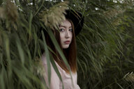 Portrait of serious Asian woman standing in field of tall grass - BLEF00628