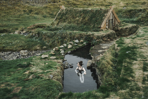 Caucasian woman swimming in pond near rural house - BLEF00694