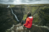 Caucasian woman sitting on cliff admiring waterfall - BLEF00724