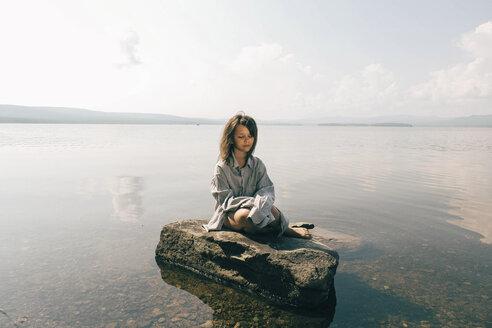 Caucasian girl sitting on rock in lake - BLEF00757