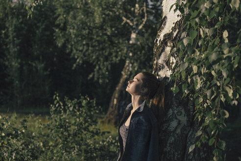 Caucasian woman leaning on tree trunk - BLEF00763