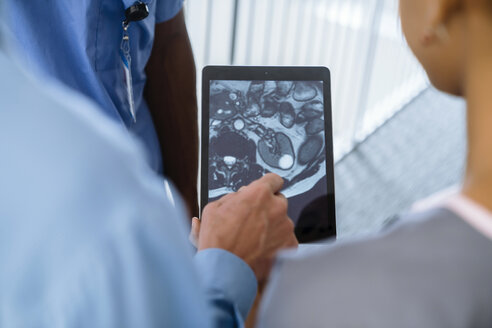 Close up of doctor and nurses viewing image on digital tablet - BLEF00766