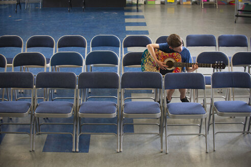 Caucasian boy sitting in row of chairs practicing guitar - BLEF00793