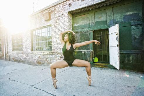 Sunbeams on mixed race woman dancing in city - BLEF00961