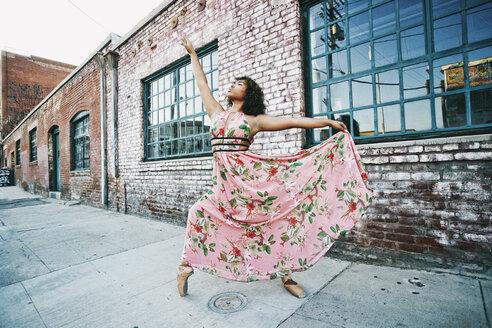 Mixed race ballet dancer wearing dress on sidewalk - BLEF00964