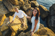 Caucasian couple climbing on rocks at beach - BLEF01042
