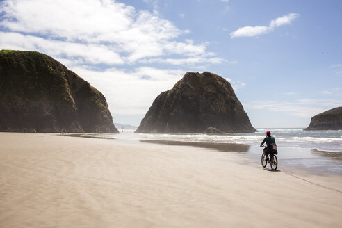 Distant Caucasian woman riding bicycle on beach - BLEF01054
