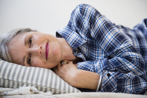 Smiling Caucasian woman laying on pillow - BLEF01090