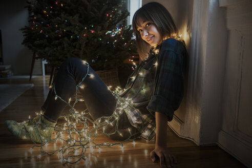 Mixed Race woman sitting on floor wrapped in string lights near Christmas tree - BLEF01102
