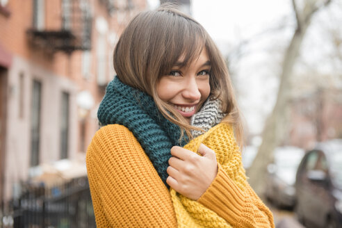 Portrait of smiling Mixed Race woman wearing scarf in city - BLEF01108