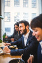 Smiling businessman eating meal with female colleagues at table in creative office - MASF11894