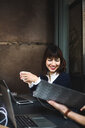 Smiling female entrepreneur holding coffee cup discussing with colleague over document at desk in office - MASF11966