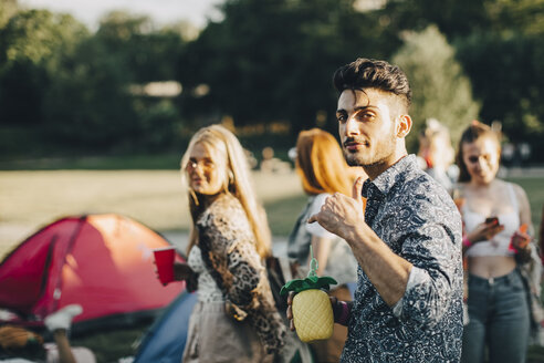 Portrait of smiling man gesturing while enjoying with friends at concert - MASF12074