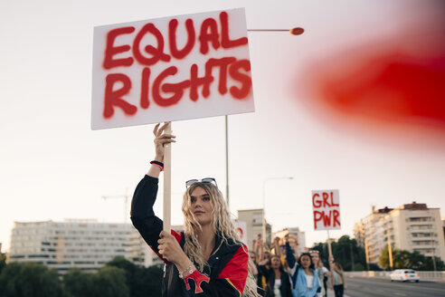 Women protesting with friends for equal rights in city against sky - MASF12083