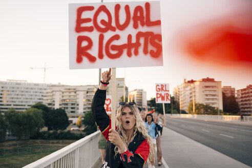 Women with poster shouting while marching for equal rights on bridge in city - MASF12086