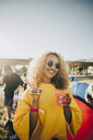 Portrait of smiling woman gesturing while enjoying drink in music festival - MASF12122