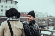 Portrait of confident smiling woman wearing warm clothing while standing with friend in city during winter - MASF12137