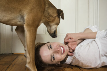Dog standing over Caucasian woman laying on floor - BLEF01186