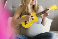 Caucasian and expectant mother playing small yellow guitar - BLEF01198