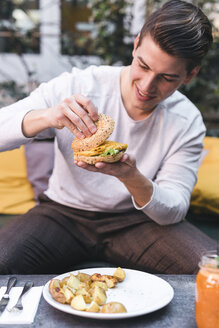 Young man sitting on couch in a restaurant having a vegan burger for lunch - FBAF00450