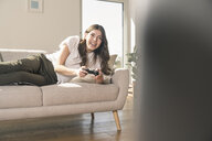 Happy young woman playing video game at home - UUF17255