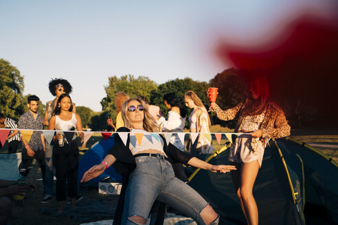 Young friends performing limbo dance while camping in music festival - MASF12158