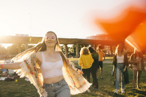 Smiling woman dancing with friends in background at event on sunny day - MASF12182