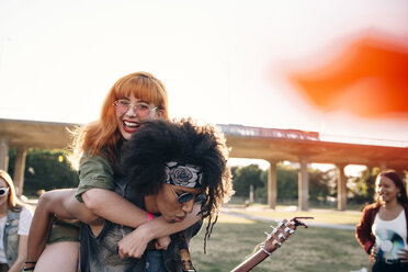 Young man piggybacking happy friend while enjoying in music festival - MASF12188