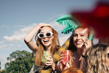 Cheerful female friends enjoying drinks at music concert against sky in summer - MASF12215
