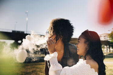 Playful woman looking at man exhaling smoke bubbles in music festival - MASF12221