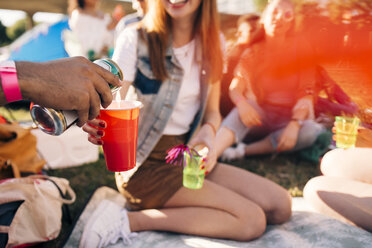 Cropped image of man pouring alcohol in friend's glass at party in festival - MASF12224