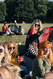 Smiling friends enjoying drink while camping on sunny day in concert - MASF12236