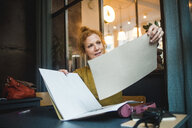 Confident mature female illustrator holding papers at desk in creative office - MASF12248