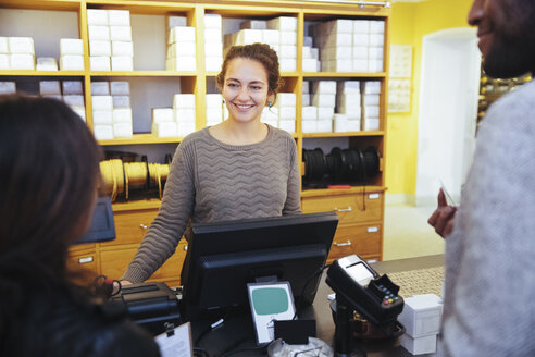 Smiling young female cashier looking at customer standing in furniture store - MASF12272