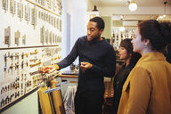 Young male sales clerk showing metal latches to female customers standing at home improvement store - MASF12278