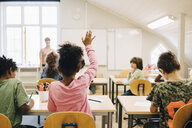 Rear view of boy raising hand while answering in class at elementary school - MASF12314