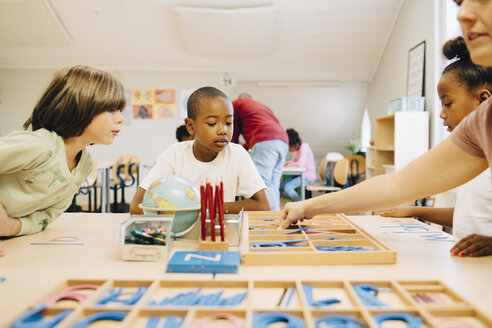 Students learning spellings at table by teacher in classroom - MASF12320